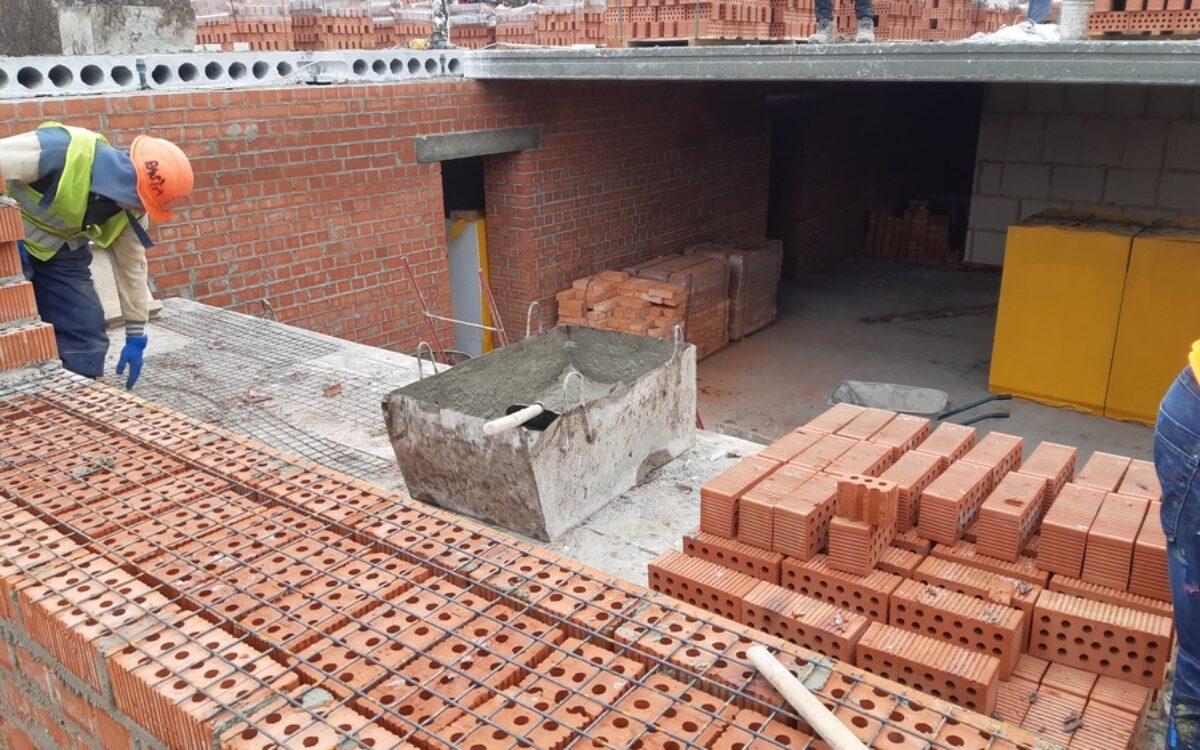процесс строительства внутренних несущих стен. Кирпичная кладка толщиной в два кирпича, дополнительное армирование